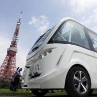 A Navya Arma autonomous shuttle bus moves past Tokyo Tower during a test drive Tuesday. | BLOOMBERG