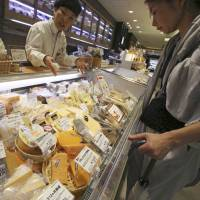 A customer looks at various types of imported cheese on sale at a department store in Tokyo on Saturday. Cheese was one of the sticking points in the free trade negotiations between Japan and European Union. | AP