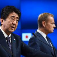 Prime Minister Shinzo Abe (left) and European Council President Donald Tusk give a news conference along with the European Commission president after an EU-Japan summit at the European Council on Thursday in Brussels. | AFP-JIJI