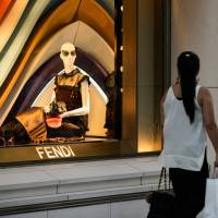 A shopper walks past a window display in a Fendi store, a brand of LVMH, in the Ginza district of Tokyo. | BLOOMBERG