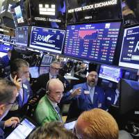 Specialist Peter Giacchi (background, center) handles the close of trading of Reynolds American on the floor of the New York Stock Exchange on July 24. | AP