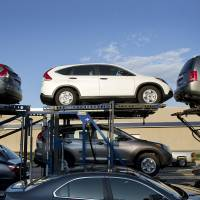 Vehicles wait to be unloaded from a truck parked at a Honda dealership in the Queens borough of New York. | BLOOMBERG