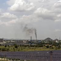 Industrial buildings stand beyond DMICDC Neemrana Solar Power Co.'s solar panels at the Rajasthan State Industrial Development and Investment Corp.'s industrial complex in Neemrana, India, in June.   BLOOMBERG