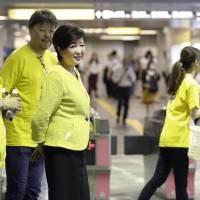 Tokyo Gov. Yuriko Koike (second from left) watches early morning commuters Tuesday at Shinjuku-Nishiguchi Station on the Oedo Line as the metropolitan government kicked off a two-week campaign to encourage staggered commuting. | KYODO