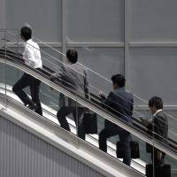 Office workers ride an escalator in Tokyo in June. Japan needs to resolve its severe labor shortage to achieve sustainable economic growth, according to a new government report. | BLOOMBERG