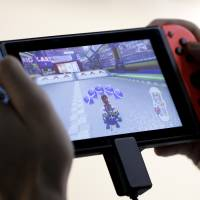 A person plays Nintendo's 'Mario Kart 8 Deluxe' video game on a Switch console. | BLOOMBERG
