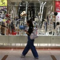 A pedestrian walks past a window display of a Daimaru Inc. department store in Osaka on July 26. | BLOOMBERG