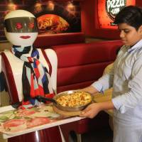 A young customer picks up a pizza from a tray carried by a robot waitress Tuesday at a pizza restaurant in Multan, Pakistan. | AFP-JIJI