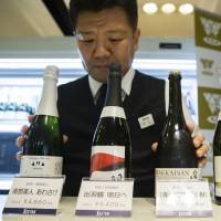 A member of the Japan Awasake Association displays bottles of sparkling sake, including one brewed by Nanbu-Bijin (left), at the association's booth during a Sake Marche event at the Isetan Shinjuku department store in Tokyo on June 28. | BLOOMBERG