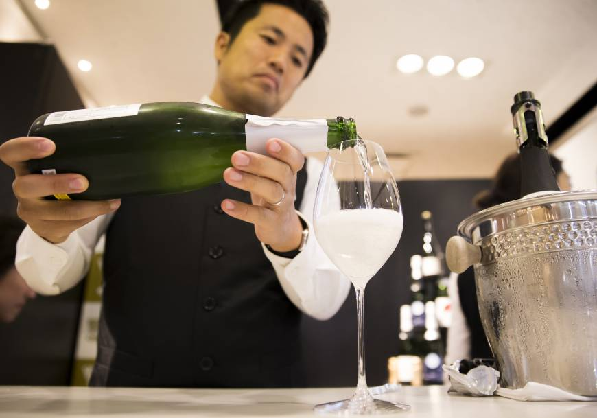 A member of the Japan Awasake Association pours a glass of Nanbu Bijin Asa Wake Sparkling sake, brewed by Nanbu Bijin Co., during a Sake Marche event at the Isetan Shinjuku department store in Tokyo on June 28.