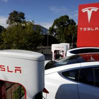 Tesla Model X cars are charged by high-speed superchargers at a Tesla electric car dealership in Sydney in May. Tesla has produced its first Model 3 sedan, which carries a relatively affordable sticker price.   REUTERS