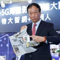 Terry Gou, founder and chairman of Foxconn, tears a newspaper bearing a front page article about Foxconn losing the acquisition battle for Toshiba Corp.'s chip business, during a news conference in Taipei on June 22. | REUTERS