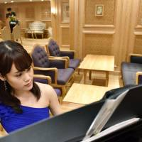 A pianist demonstrates her technique Friday in a special lounge at Tokyu Yokohama Station for passengers of The Royal Express luxury train.   KYODO