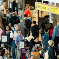 Travelers wait in line at the security checkpoint at Baltimore/Washington International Airport in Baltimore, Maryland, in June. | AFP-JIJI