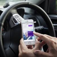 A driver for the Uber Technologies Inc. ride-hailing service uses the company's app on a smartphone in Singapore. | BLOOMBERG
