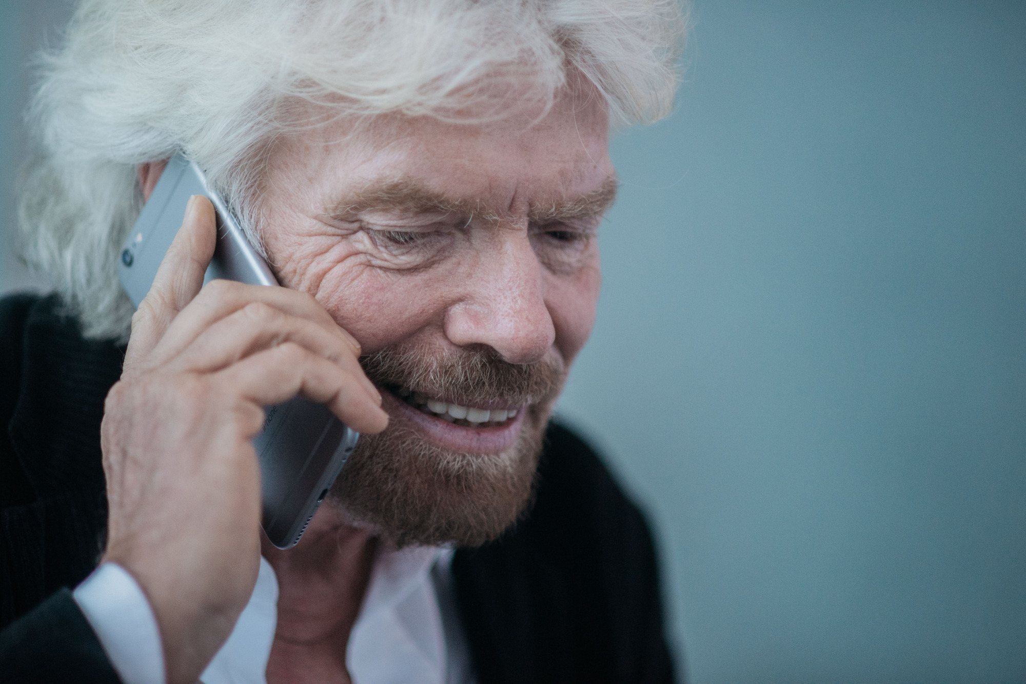 Billionaire Richard Branson, founder of Virgin Group Ltd., speaks on a smartphone during an interview in Hong Kong on Wednesday. Virgin Galactic will conduct powered flights with new SpaceShipTwo craft roughly every three weeks after its restart, Branson said in the interview. | BLOOMBERG