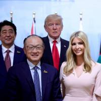 Prime Minister Shinzo Abe stands with World Bank President Jim Yong Kim (from left), U.S. President Donald Trump, Ivanka Trump, German Chancellor Angela Merkel and Canadian Prime Minister Justin Trudeau for a group photo at the Women's Entrepreneurship Finance event during the Group of 20 leaders summit in Hamburg, Germany, on Saturday. | REUTERS