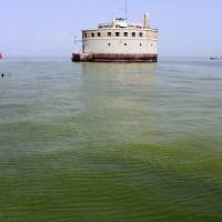 The water intake crib for the city of Toledo, Ohio, is surrounded by an algae bloom on Lake Erie, about 2.5 miles off the shore of Curtice, Ohio, in August 2014. Researchers are working on creating an early warning system that can spot when algae begins showing up on hundreds of lakes across the U.S., using real-time data from satellites that already monitor harmful algae hotspots on Lake Erie in Ohio and on the Chesapeake Bay along the East Coast. | AP