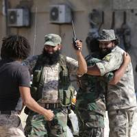 Members of the Libyan army's special forces celebrate after the liberation of the last region of Islamist militants in their last stronghold in Benghazi, Libya, Wednesday. | REUTERS