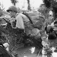 A paratrooper of the 173rd U.S. Airborne brigade crouches with women and children in a muddy canal as intense Viet Cong sniper fire temporarily pins down his unit during the Vietnamese War near Bao trai in Vietnam in 1966. | AP