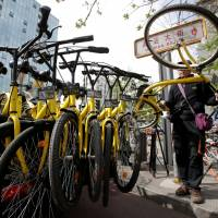 A worker for the bike-sharing company Ofo gathers bicycles ahead of the evening rush hour, in Beijing on April 12. | REUTERS