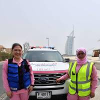 Filipino Dr. Maria Lagbes (left) and a driver stand next to a pink ambulance of the Women Responders team in Dubai on Thursday. Four women, two medics and two drivers are leading the pilot project for a women-only pink ambulance service that aims to expedite medical care by helping patients feel more at ease. | AFP-JIJI