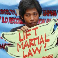 A protester holds a placard during a protest in Manila on Tuesday of the extension of martial law on Mindanao Island in the southern Philippines. | AP