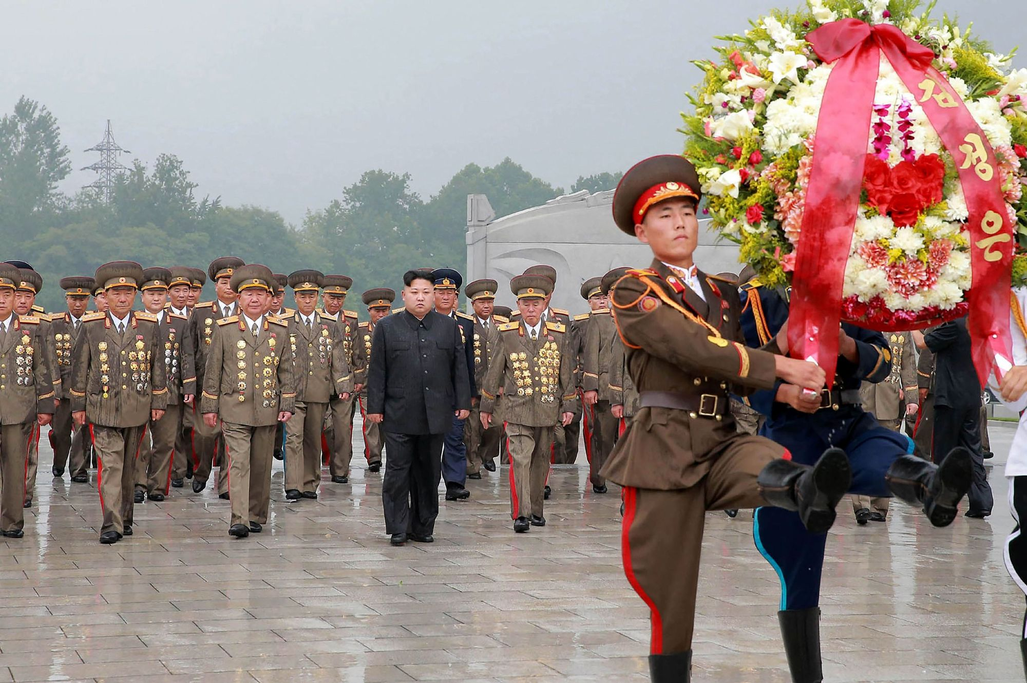 North Korean leader Kim Jong Un (black suit) visits the Fatherland Liberation War Martyrs' Cemetery in Pyongyang on Thursday. | AFP-JIJI