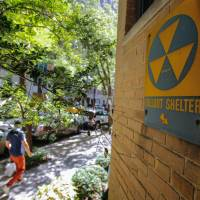 People pass by a Fallout Shelter sign in the Manhattan boroughof New York on Sunday.   AFP-JIJI