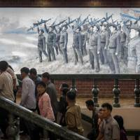 People walk up stairs before a propaganda poster showing Korean People's Army (KPA) soldiers at a museum in Sinchon, south of Pyongyang Saturday. North Korea said Sunday its latest ICBM test was a 'warning' targeting the U.S. for its efforts to slap new sanctions on Pyongyang and threatened a counterstrike if provoked militarily by Washington.   AFP-JIJI