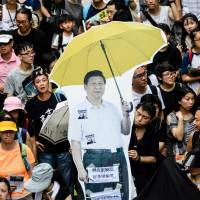 A cardboard cutout of Chinese President Xi Jinping holding a yellow umbrella, a symbol of the pro-democracy 'Umbrella Movement,' is carried during a protest march in Hong Kong on Saturday. | AFP-JIJI