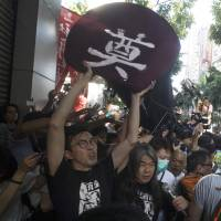 Hong Kong pro-democracy activists carry a replica of a casket with a Chinese character meaning 'respect for the dead' on Saturday as they tried to march to the venue where official ceremonies were being held to mark the 20th anniversary of the handover from British to Chinese rule. | AP