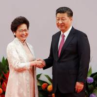 Hong Kong Chief Executive Carrie Lam shakes hands with Chinese President Xi Jinping after she took the oath of office on Saturday, the 20th anniversary of the city's handover from British to Chinese rule. | REUTERS