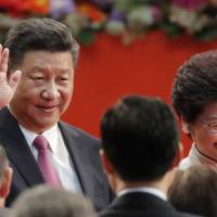Chinese President Xi Jinping and new Hong Kong Chief Executive Carrie Lam leave after she took the oath of office for a five-year term at the Hong Kong Convention and Exhibition Center on Saturday. | AP