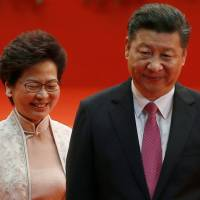 Hong Kong Chief Executive Carrie Lam and Chinese President Xi Jinping walk after he swore her into office on Saturday, the 20th anniversary of the city's handover from British to Chinese rule. | REUTERS