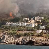 Woodland fires burn near a tourist resort where, according to firefighter reports, some several hundred tourists have been evacuated by land and sea, in the Sicilian town of San Vito lo Capo, southern Italy, Wednesday. Wildfires have been raging for days and Italian firefighters said Wednesday they were responding to 887 fires throughout Italy, 628 of which regarded vegetation and woodlands. | ITALIAN FIREFIGHTERS VIGILI DEL FUOCO / VIA AP