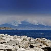 Smoke rises from wildfires burning on the slopes of Mount Vesuvius volcano as the Castel dell'Ovo castle in seen in the foreground, in Naples, Italy, Wednesday. Firefighters are battling wildfires throughout southern Italy, including along the slopes of the volcano Vesuvius. | CIRO FUSCO / ANSA / VIA AP