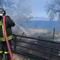 An Italian firefighters sprays water to extinguish a fire that broke out on the Posillipo hill in Naples, Italy, Monday. Wildfires have been ravaging swaths of Italy, mostly in the south, where the Coldiretti agricultural lobby says July rain levels were down 83 percent while temperatures were around 3 degrees Celsius higher. About 2,500 hectares (6,180 acres) of pasture have been destroyed in Sicily alone. | CIRO FUSCO / ANSA / VIA AP