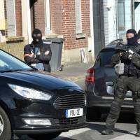 Police officers of an anti-terrorim unit and of French intelligence agency (DGSI) patrol a street in Wattignies, northern France, after a man was arrested during a French-Belgian anti-terrorist operation Wednesday. Four people have been arrested and an arms cache found after overnight terror raids in Brussels linked to a bikers' club called the Kamikaze Riders, federal prosecutors said Wednesday. | AFP-JIJI