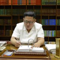 from North Korea's official Korean Central News Agency (KCNA) on July 29, 2017 North Korean leader Kim Jong-Un signs documents for the test launch of an intercontinental ballistic missile, the Hwasong-14, at an undisclosed place in North Korea on Thursday. | AFP-JIJI