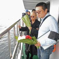 This handout photo provided by the Shenyang Municipal Information Office shows the late Nobel laureate Liu Xiaobo's wife, Liu Xia, and her younger brother, Liu Xiaoxuan, holding flowers as they bury Liu's ashes at sea off the coast of Dalian, Liaoning Province, on Saturday. The body of China's late Nobel laureate Liu Xiaobo was cremated after a private ceremony attended by his wife and friends, two days after the dissident lost a battle with cancer while in custody. | SHENYANG MUNICIPAL INFORMATION OFFICE / VIA AFP-JIJI