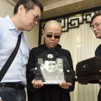 In this Saturday file photo provided by the Shenyang Municipal Information Office, Liu Xia, wife of jailed Nobel Peace Prize winner and Chinese dissident Liu Xiaobo, holds a portrait of him during his funeral at a funeral parlor in Shenyang in northeastern China's Liaoning Province. The photo shows (from left) Liu Hui, younger brother of Liu Xia, Liu Xia and Liu Xiaoxuan, younger brother of Liu Xiaobo holding his cremated remains. | SHENYANG MUNICIPAL INFORMATION OFFICE / VIA AP, FILE