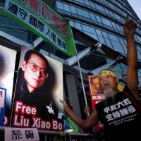 Demonstrators outside the Chinese Foreign Ministry in Hong Kong October 8, 2010 demand the release of jailed activist Liu Xiaobo. The placard reads 'Congratulate Liu Xiaobo winning Nobel Peace Prize' and 'Respect the spirit of Nobel Peace Prize. Release Liu Xiaobo and all dissidents.' | REUTERS