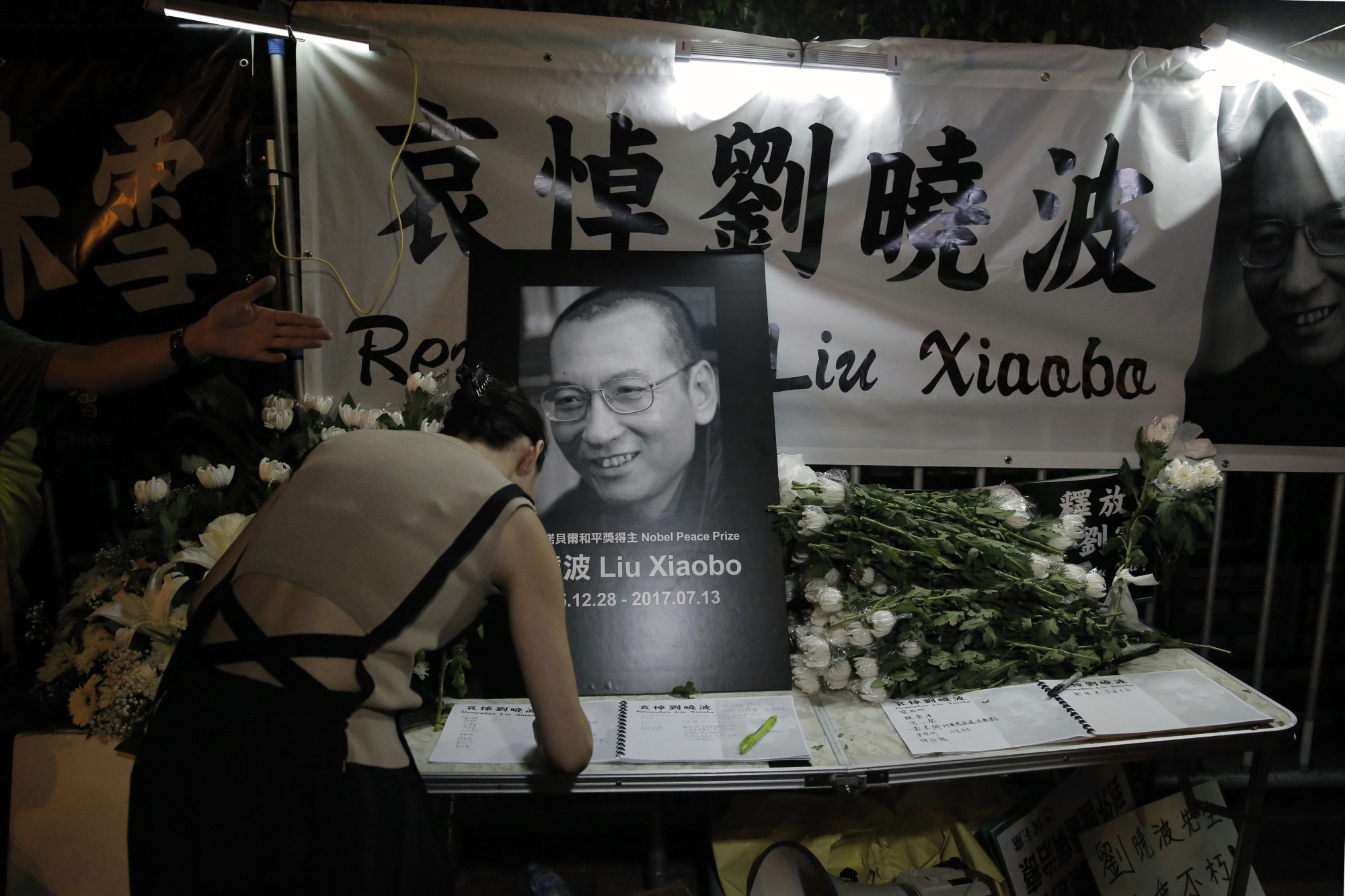 A protester signs a condolence book for jailed Chinese Nobel Peace laureate Liu Xiaobo during a demonstration outside the Chinese liaison office in Hong Kong on Thursday. Government officials in the northeast Chinese city of Shenyang said the same day that Liu had died from liver cancer.   AP