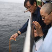 Liu Xia, wife of deceased Chinese Nobel Peace Prize-winning dissident Liu Xiaobo, attends his sea burial with other relatives off the coast of Dalian, China, on Saturday. | REUTERS