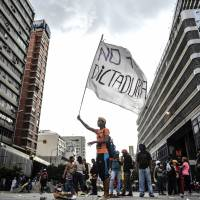 An opposition activist hols a flag reading 'No more dictatorship' during a blockade to protest Venezuelan President Nicolas Maduro in Caracas on Tuesday. Venezuela's government on Tuesday defiantly brushed aside U..S President Donald Trump's threat of economic sanctions by saying it will go ahead with the election of a controversial body to rewrite the country's constitution. | AFP-JIJI