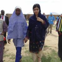 Pakistani activist Malala Yousafzai (center right) is welcomed by students and a staff from UNICEFF during a visit to the camp of people displaced by Islamist extremists in Maiduguri ,Nigeria, Tuesday. Nobel Peace Prize laureate Malala was greeted with cheers Tuesday by dozens of young women in northeastern Nigeria, where she spoke out for the many girls abducted under Boko Haram's deadly insurgency. | AP