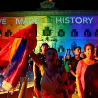 People celebrate in front of the rainbow-color-lit Auberge de Castille, the office of Prime Minister Joseph Muscat, after the Maltese parliament voted to legalize same-sex marriage on the Roman Catholic Mediterranean island, in Valletta Wednesday. | REUTERS