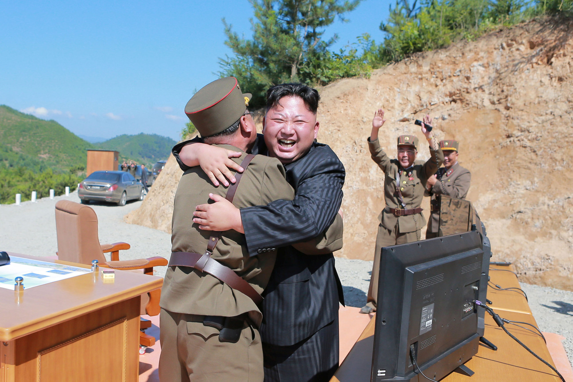 North Korean leader Kim Jong Un reacts with scientists and technicians of the country's Academy of Defense Science after the test-launch of the Hwasong-14 intercontinental ballistic missile Tuesday. | KCNA / VIA REUTERS