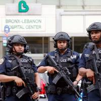 Police officers patrol the scene after a shooting incident Friday inside the Bronx-Lebanon Hospital Center in New York City. | REUTERS